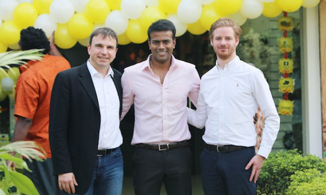 3 men standing in front of yellow balloons