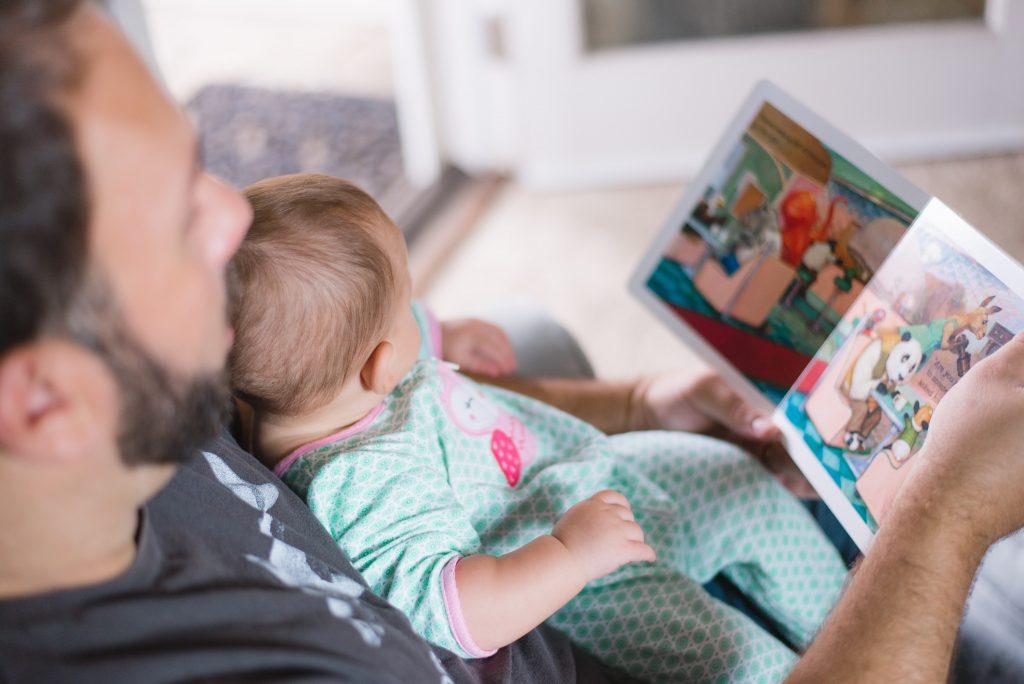 Man reading children's book to baby